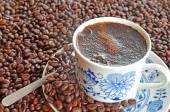 Cup of coffee and pile of coffee beans — Stock Photo