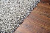 White shaggy carpet on brown wooden floor — Stok fotoğraf
