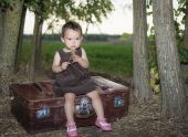 Little girl on a suitcase blowing a dandelion — Stock fotografie