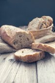 Half bread and slices of it in a basket — Stock Photo