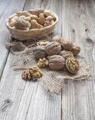 Heap of walnuts in a bowl  and some around — Stock Photo
