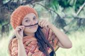 Beautiful girl with hairdo putting braid's tail end like moustache — Stok fotoğraf