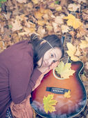 Beautiful girl resting on autumn leafs with guitar — Stock Photo