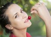 Young girl eats cherry outdoor — Foto de Stock