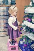 Beautiful girl decorating christmass tree — Stock Photo