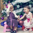 Little girls sitting near the Cristmas tree — Stock Photo #63929785