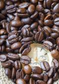 Closeup watch in the lots of natural coffee beans — Stock Photo