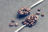 Coffe beans in steel spoons on black — Stock Photo