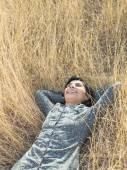 Beautiful Young woman lying on hay — Stock Photo