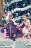 Little girls sitting near the Cristmas tree — Fotografia Stock