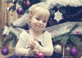 Little blonde girl near the Christmas tree — Stock Photo