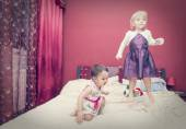 Two little girls jumping on a bed — Stock Photo