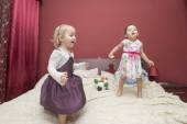 Little girls jumping on a bed — Stock Photo