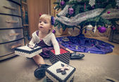 Little blonde girl searching for presents near the Christmas tree — Stockfoto