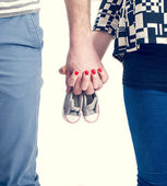 Future parents holding hands and a pair of little shoes over white background — Stock Photo