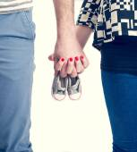 Future parents holding hands and a pair of little shoes over white background — Foto de Stock