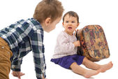 Two little kids disputing a suitcase — Stock Photo