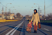 Lovely girl and mother with suitcase on the railway — Stock Photo
