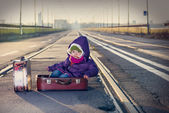Little girl sitting in a suitcase near the railway — Stock Photo
