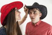 Young couple with cowboy hats and glasses making silly faces on white background — Stock Photo