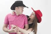 Young couple with cowboy hats making silly faces on white background — Stok fotoğraf