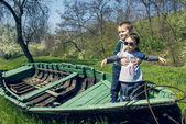 Little girl with brother having fun in an old boat — Stock Photo