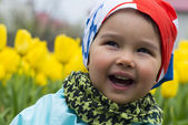 Portrait of a beautiful little girl with tulips in background — Stock Photo