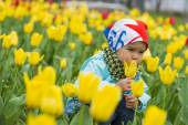 Beautiful little girl on a field of tulips — Stock Photo