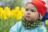 Beautiful little girl with a field of tulips in background — Stock Photo
