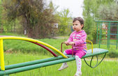 Little cute girl sits on seesaw in a sunny day — Fotografia Stock