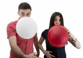Young couple announcing their baby while blowing balloons — Stock Photo