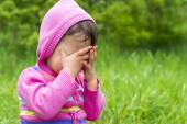 Little girl is playing hide-and-seek hiding face — Stock Photo