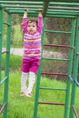 Happy little girl climbing on outdoor playground — Stock Photo