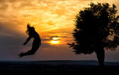 Silhouette of a beautiful girl jumping over sunset — Stock Photo