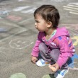 Happy little girl draw with chalk on the pavement in the park — Stock Photo #75095955