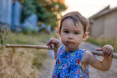 Little and dirty girl with her stick — Stock Photo