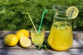 Lemonade in the jug and lemons on the table outdoor — Stock Photo