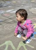Happy little girl draw with chalk on the pavement in the park — Stock Photo