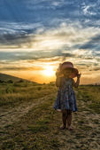 Beautiful girl with hat at the sunset — Stock Photo