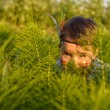 Funny little girl as indian  hiding behind grass — Stock Photo #75624345