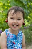 Sweet little girl with cherry earrings — Stock Photo