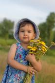 Cute little girl holding an bucket of yarrow flowers — Stock Photo