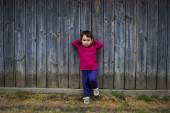 Summer portrait of a cute little girl of two years old by the fence — Stock Photo