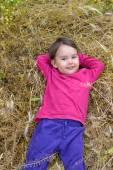 Porträtt av en liten flicka leende som hon ligger i gräset — Stockfoto