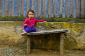 Two years old  girl sitting on rustic bench — Stock Photo