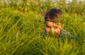 Funny little girl as indian  hiding behind grass — Stock Photo