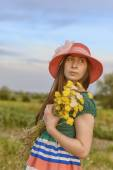 Portrait of a young female standing in field holding flowers wearing red hat — Stock Photo