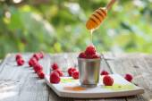 Raspberry in a cup with flowing honey from a dizzler, on wood ta — Stock Photo