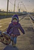 Little girl with a suitcase near the railway — Stock Photo