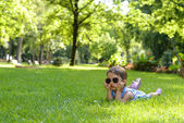 Cute little toddler girl laying in the grass on a sunny summer day — Stock Photo
